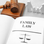 Book opened to Family Law page with scale graphic, gavel and block in background